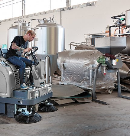 A man cleaning the factory floor using a Mach 5 Floor Sweeper