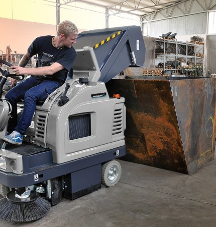 A man is emptying the Mach 5 Floor Sweeper into a skip