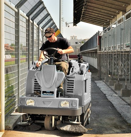 A man cleaning the floor outside with a Mach 5 Floor Sweeper