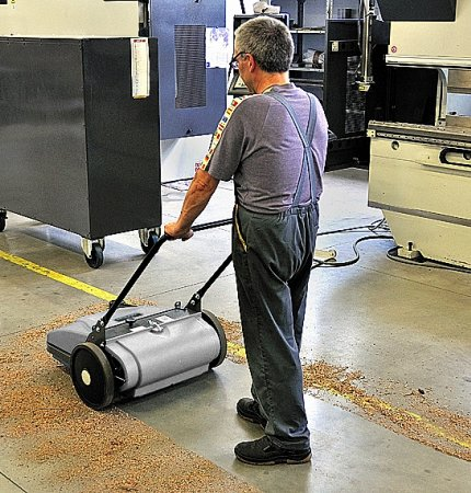 Cleaning the floor with A young man behind one of our Mach MEP Floor Sweepers